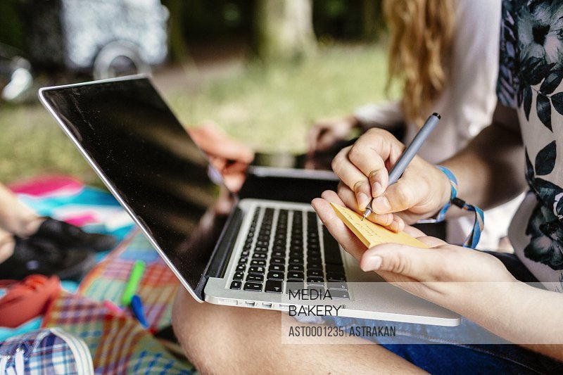 Midsection of student writing on adhesive note while sitting with laptop at park