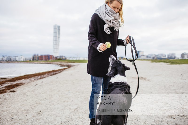 Woman holding ball while standing with dog on beach