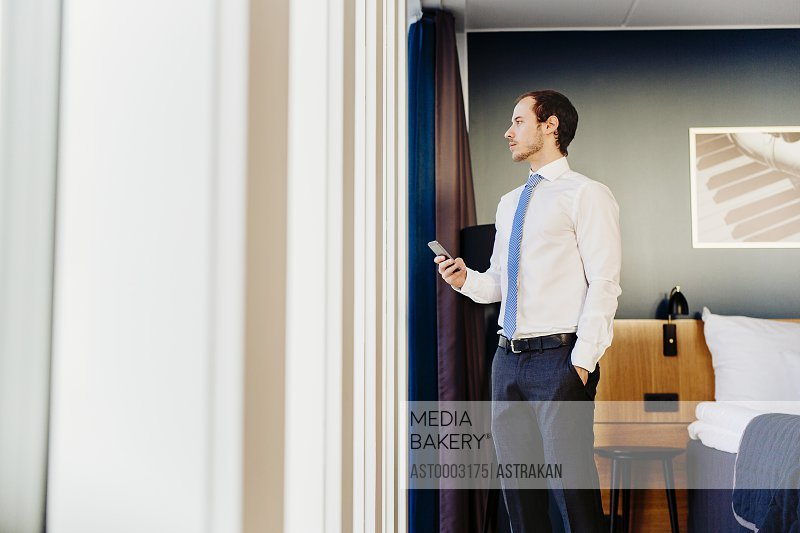 Confident businessman looking through window while standing in hotel room