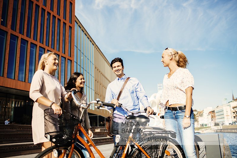 Happy friends with bicycles standing outside concert hall in Malmo Live