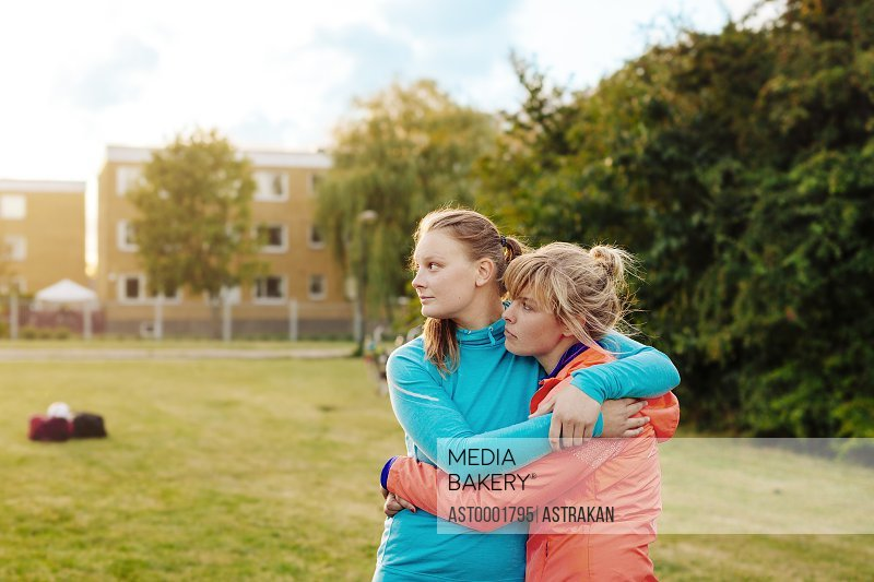 Young sporty sisters looking away while embracing at park