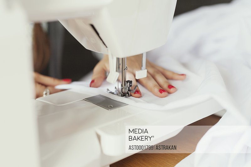 Cropped hands of fashion designer using sewing machine