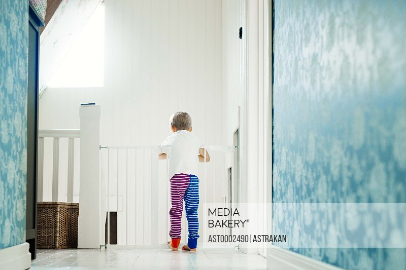 Full length rear view of boy leaning on railing at home