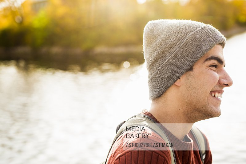 Profile shot of happy young man wearing knit hat by lake