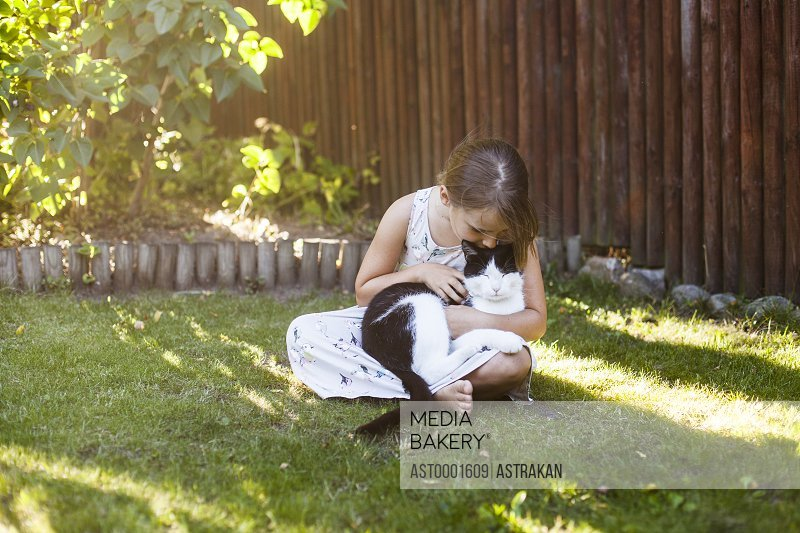 Full length of girl playing with cat in backyard