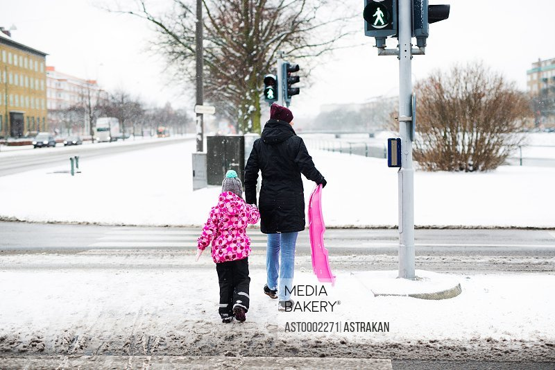 Rear view of woman and daughter with sled walking on snow covered street