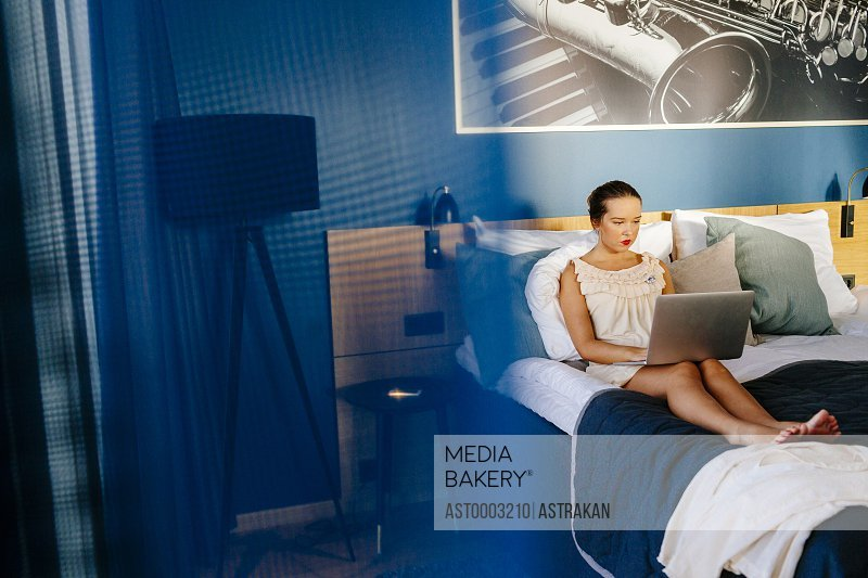 Businesswoman using laptop while relaxing on bed at hotel room