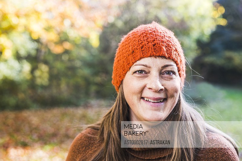 Portrait of happy mature woman wearing knit hat in forest