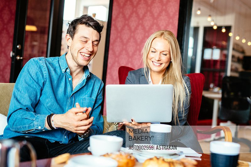 Happy business colleagues using laptop at table in office