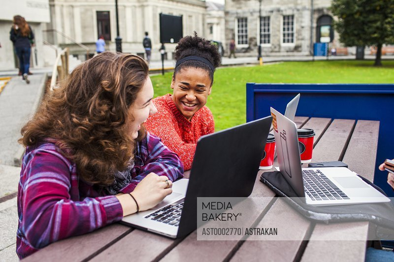 Cheerful female university students with laptops on table at campus