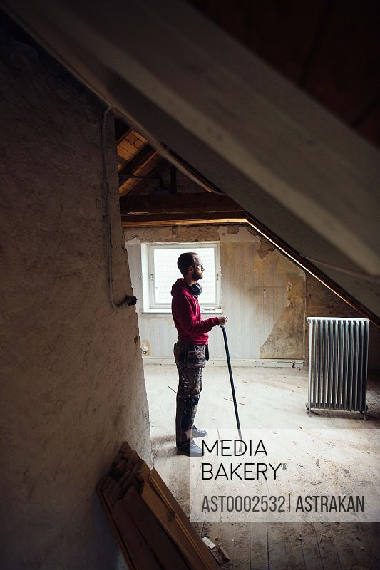 Full length side view of man with work tool renovating attic