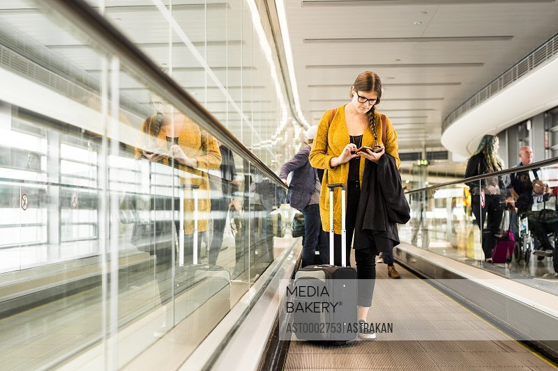 Businesswoman using smart phone on moving walkway in airport