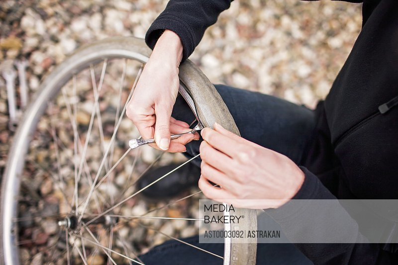 High angle view of female mechanic repairing bicycle tire