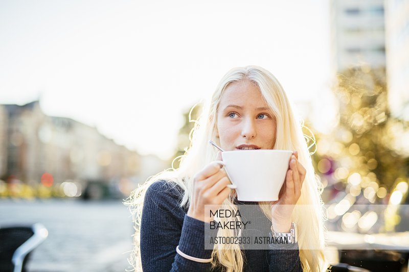 Teenage girl drinking coffee at sidewalk cafe
