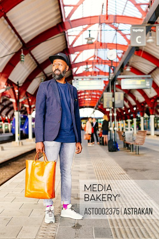 Full length of thoughtful businessman standing at railroad station