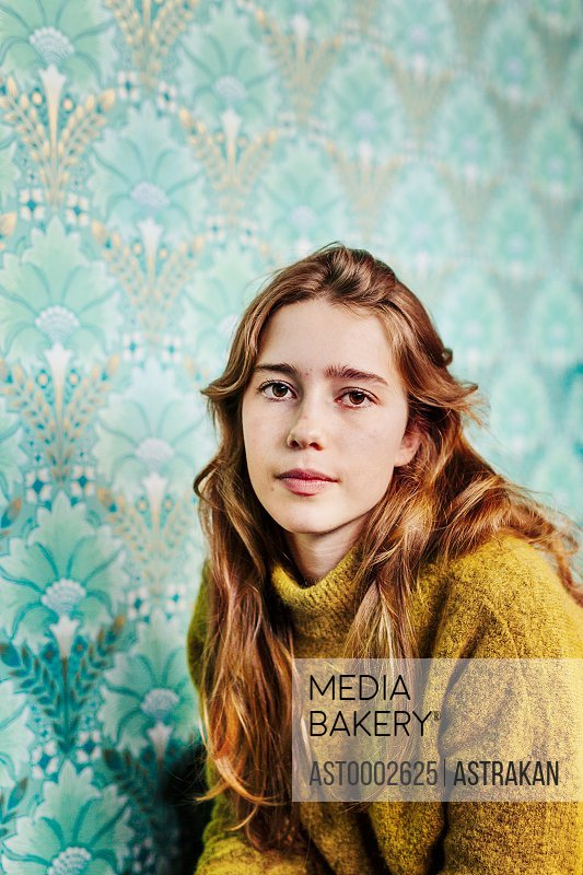 Portrait of beautiful young woman against patterned wall