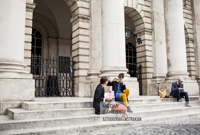 Friends sitting on steps outside building