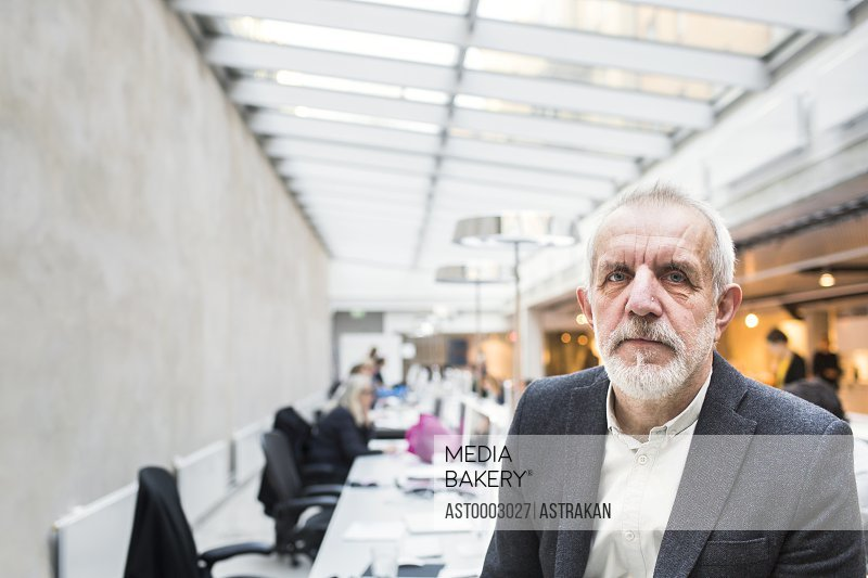 Portrait of confident senior businessman in creative office