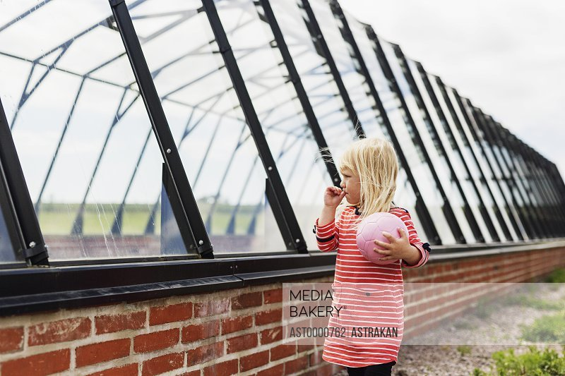 Girl holding ball while standing by glass built structure