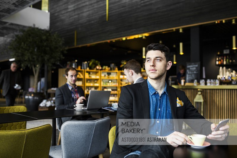 Businessman holding smart phone drinking coffee at restaurant