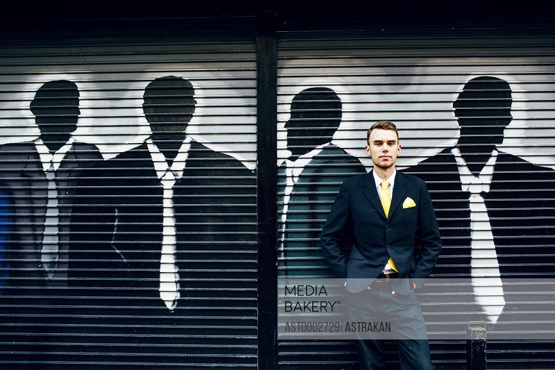 Portrait of confident well-dressed businessman standing against shutter with graffiti