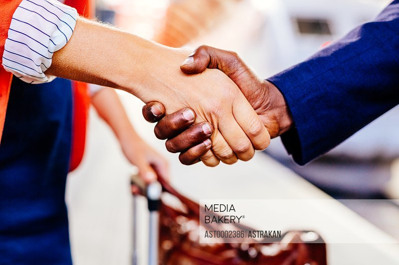 Cropped image of businesspeople shaking hands at railroad station