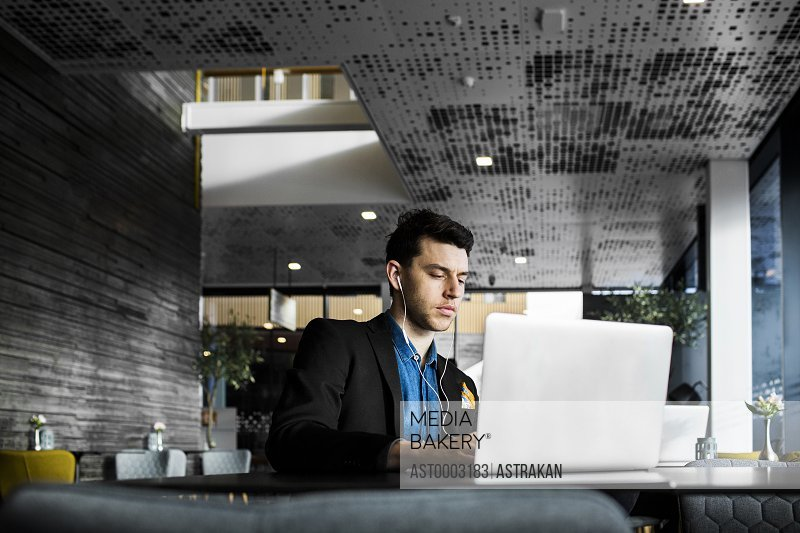 Businessman using laptop while sitting at restaurant