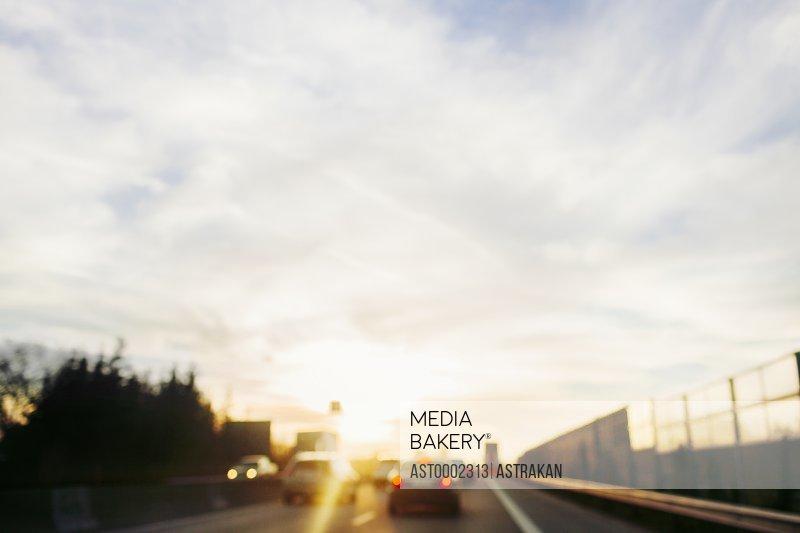 Defocused image of cars on bridge against sky on sunny day