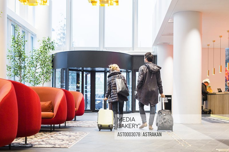 Rear view of business people with luggage walking at hotel lobby