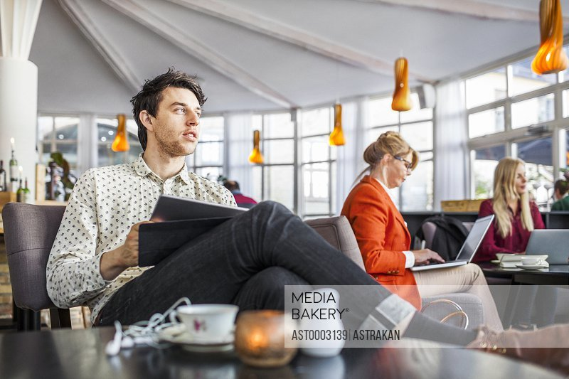 Businessman holding digital tablet while colleagues working in background