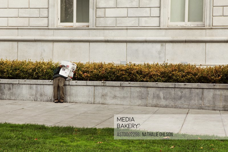Low section of man reading newspaper by building