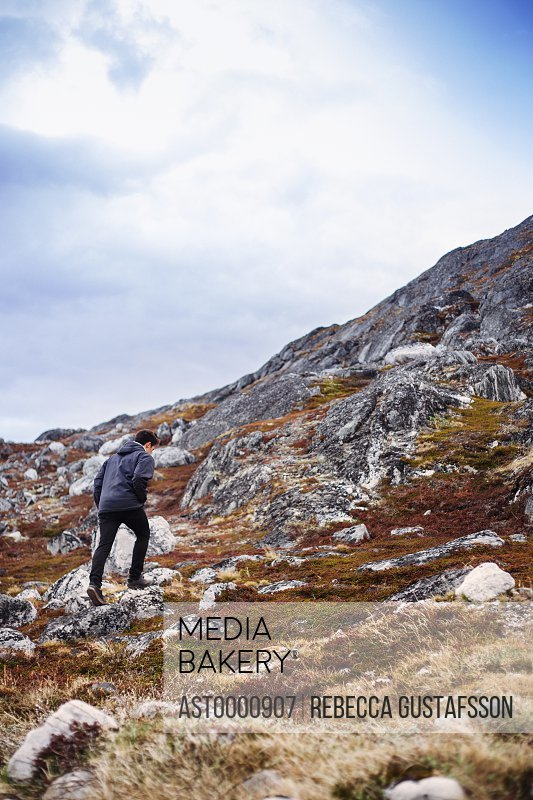 Male hiker walking on mountain against cloudy sky
