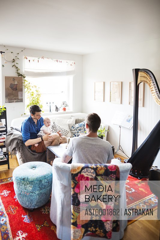 Gay men with baby girl in living room
