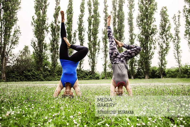 Young women doing supported headstands at park
