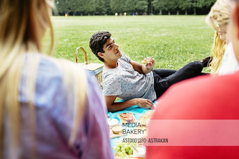 Man having food while reclining during picnic at park