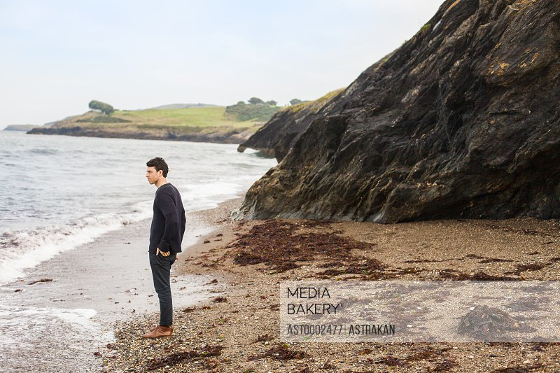 Side view of man looking away while standing on sea shore