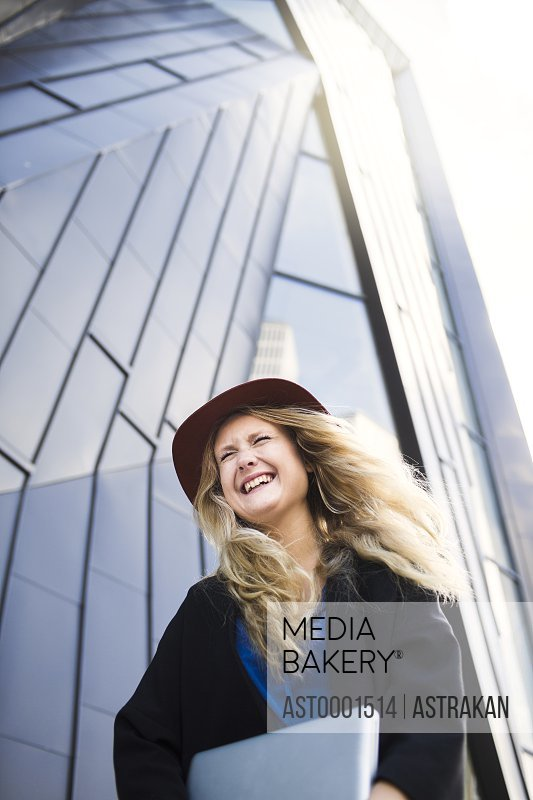 Low angle view of happy businesswoman against modern building