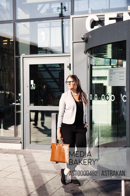 Thoughtful businesswoman standing outside railroad station
