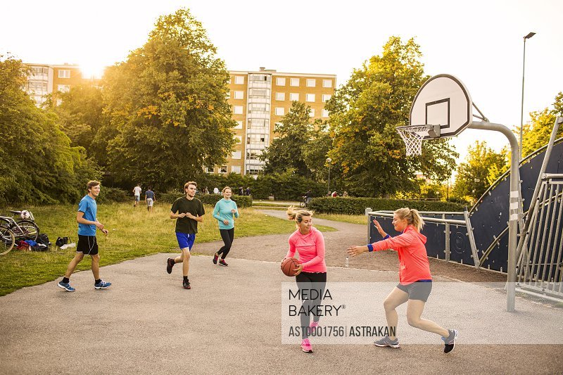 Male and female friends playing basketball at park during sunset