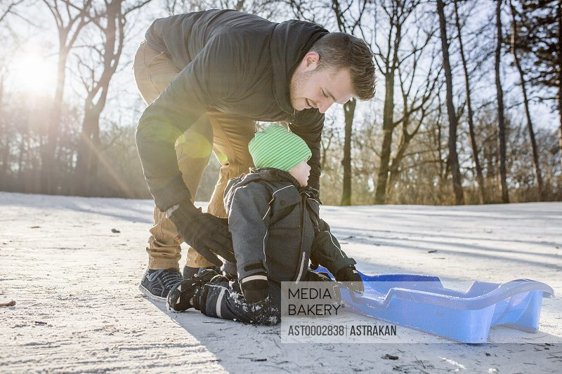 Young father preparing baby boy for tobogganing