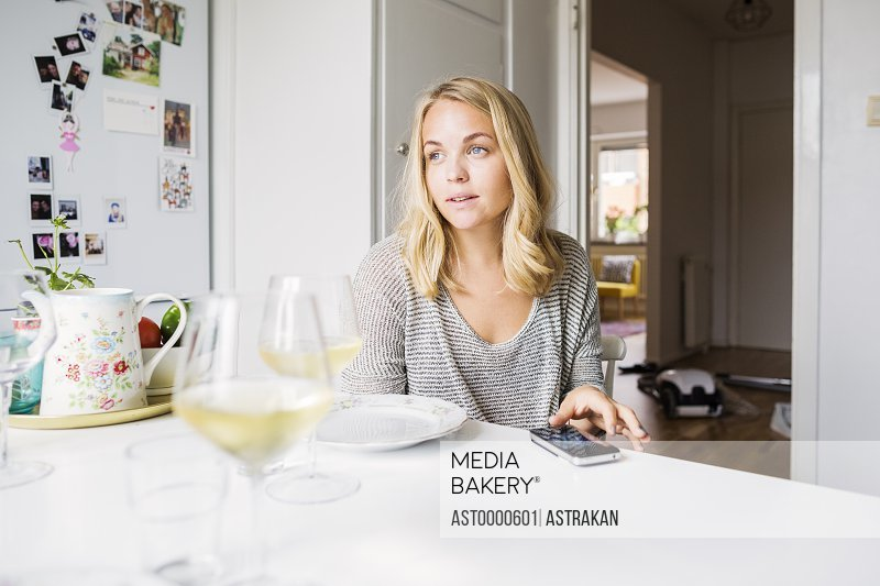 Young woman looking away while sitting at table in domestic kitchen