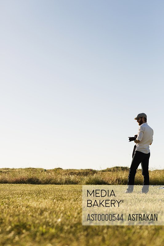 Man holding camera and standing on grassy field against clear sky