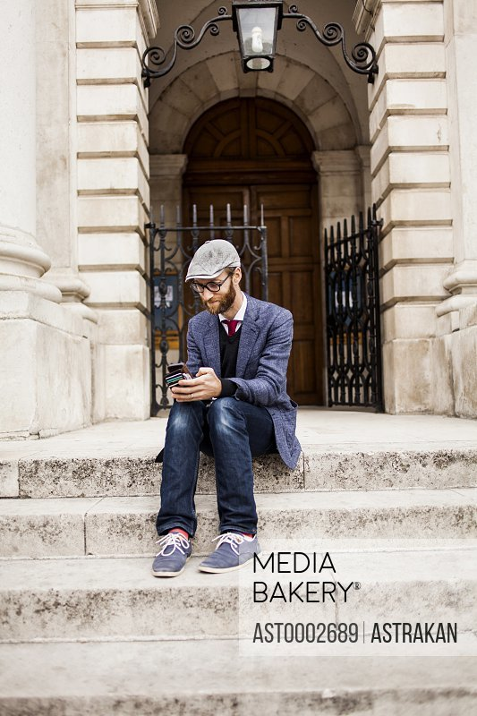 Full length of man using smart phone while sitting on steps outside building