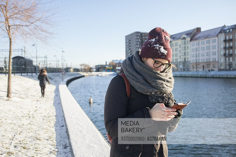 Woman using smart phone by canal in city during winter