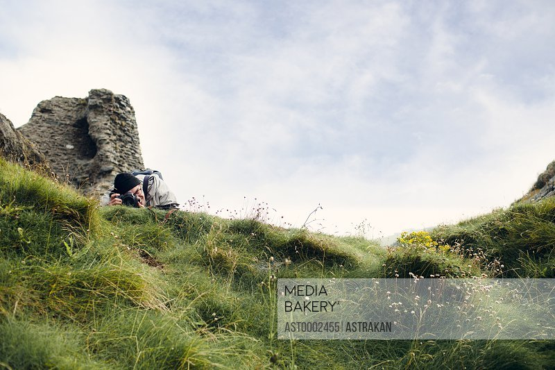 Man photographing on grassy hill against sky