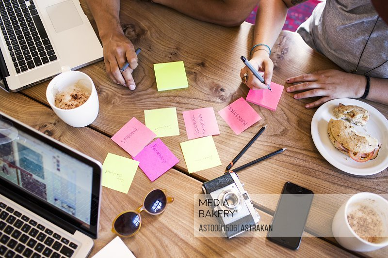 High angle view of friends writing on adhesive note while working at cafe
