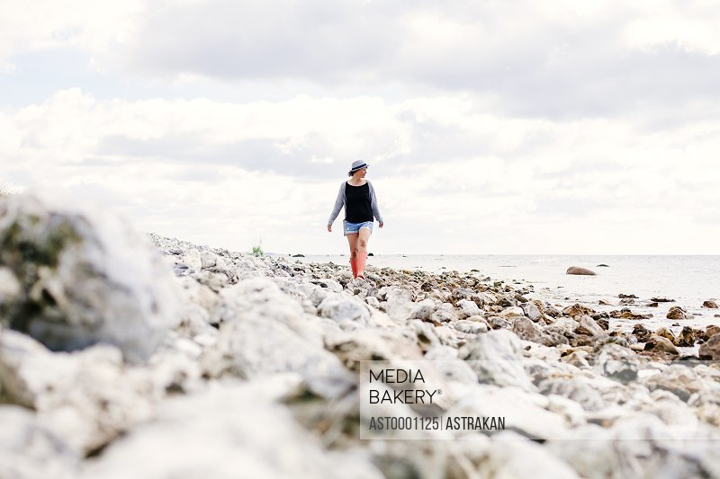 Young woman walking on beach against cloudy sky