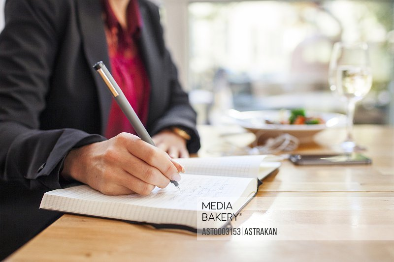 Midsection of businesswoman writing in book