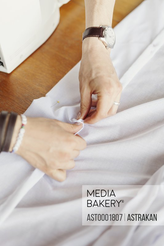High angle view of male designer pinning white textile at table