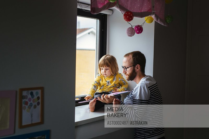Mid adult father with daughter reading story book at window